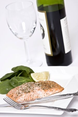 Salmon fillet with herbs macro with spinach and lemon wedge photo