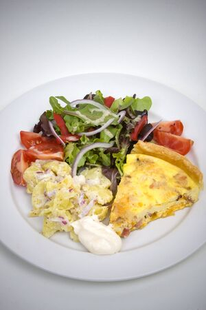 Quiche Lorraine with fresh salad on a white plate photo