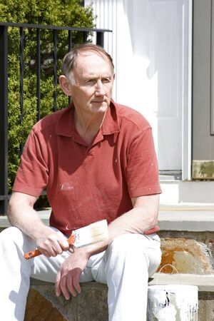 Senior man resting from house painting photo