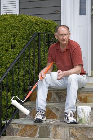 homeownership: Senior man having a coffee break from painting Stock Photo