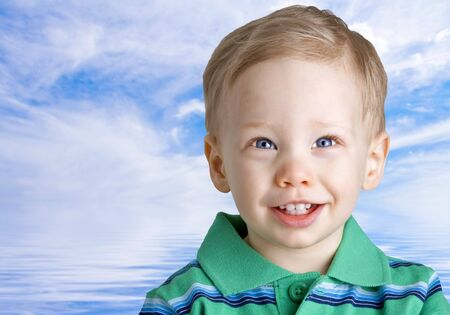 Happy boy over water and sky background photo