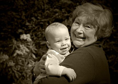 Grandmother holding happy grandson in the garden photo