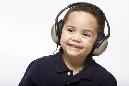 Boy listening to music with headphones on a light background photo