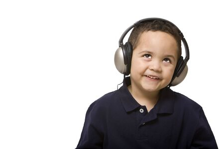Boy listening to music with headphones on white background photo