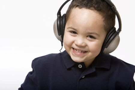 Boy listening to music with headphones on a light background Stock Photo - 3124388