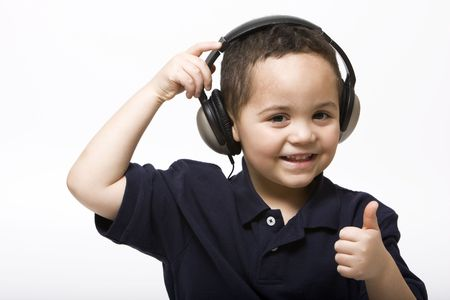 Young boy removing headphones giving thumbs up sign photo