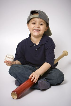Young hispanic boy with a baseball bat and ball photo