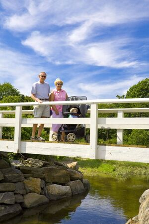 Grandparents with grandson standing on a small bridge Banco de Imagens