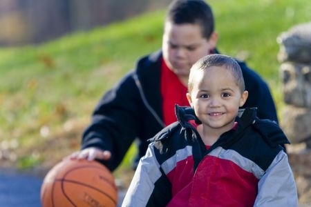 Smiling boy with older brother in background playing with basketball Stock Photo - 3124374