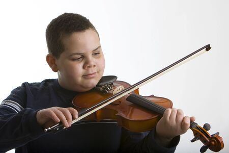 american music: Young boy playing a violin against a light background Stock Photo