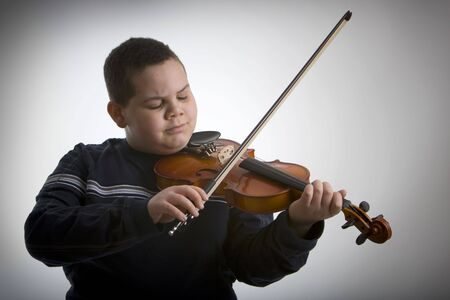Young boy playing a violin against a light vignetted background Stock Photo