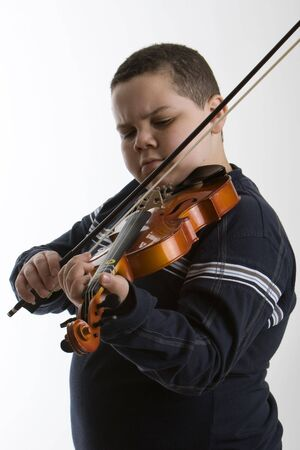 violins: Young boy playing a violin against a light background Stock Photo