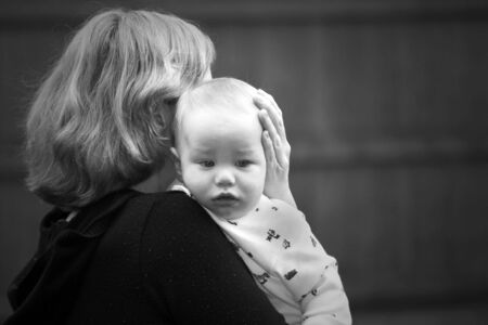 fedup: Mother comforting a sad baby in black and white Stock Photo