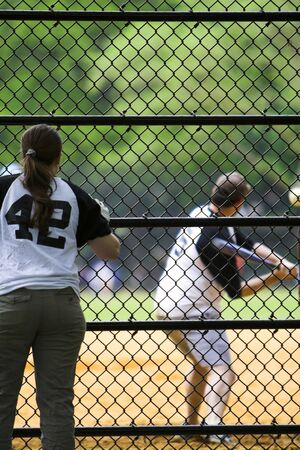 outfielders: Girl watching and supporting a team mate play baseball Stock Photo