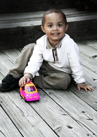 Young toddler boy playing with car with high contrast color photo