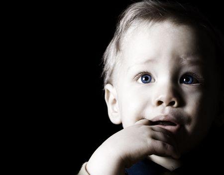 concerned: Close up childs portrait on black background Stock Photo