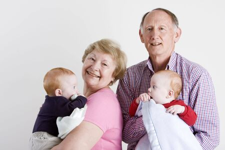 nana: Happy grandparents holding twin boys Stock Photo