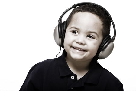 nodding: Boy listening to music with headphones on a light background