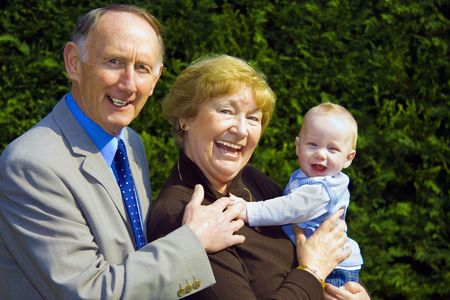 Smiling grandparents holding happy baby boy portrait