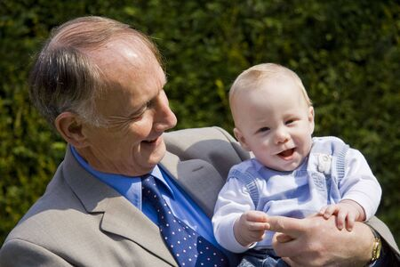 Grandfather holding smiling grandson in a sunlight garden Stock Photo - 3264266
