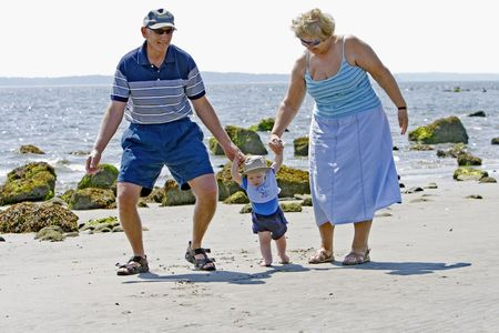 Grandparents at the beach with their grandson photo