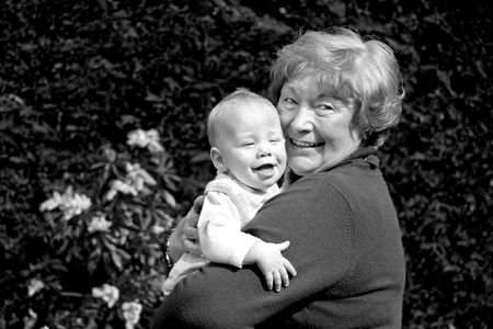 Grandmother hugging happy grandson in sunny garden photo