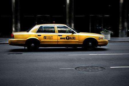 Dirty New York City yellow cab on road in evening photo