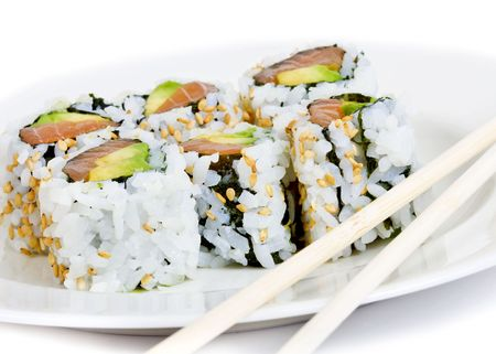 Raw fish and avocado sushi on a white plate with chopsticks photo
