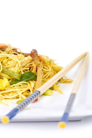 Vegetable and meat asian noodles on a plate with chopsticks photo