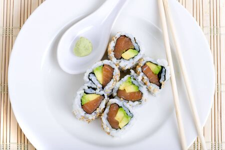 japenese: Raw fish and avocado sushi on a white plate with chopsticks and wasabi Stock Photo