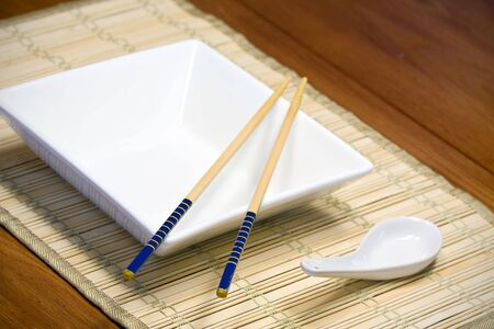 chopsticks resting on an empty white plate photo