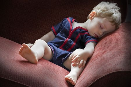 red sofa: Young tired boy taking a nap on a red sofa