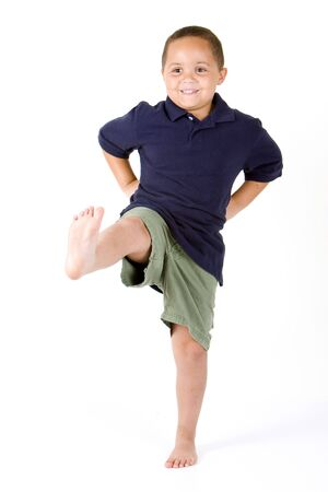 Happy mixed race boy with hands on hips and kicking a leg Stock Photo - 3421644
