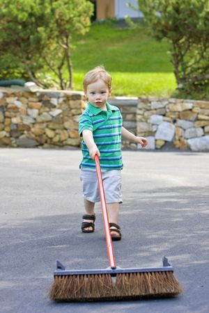 Boy with yard brush cleaning driveway outside