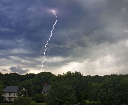Dramatic lightning strike from storm clouds over colonial style homes and woods