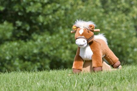 Toy rocking horse in a field with trees in background