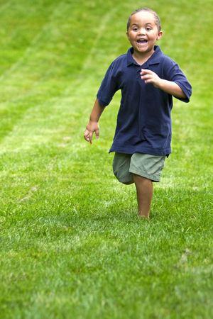 Happy mixed race boy running through green grass Standard-Bild