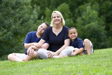 Pretty mom with her two sons outside on grass Stock Photo - 3421777