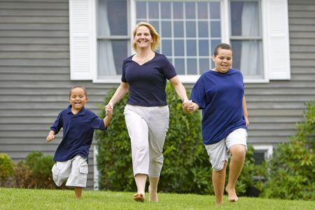Pretty mom with her two sons running outside on grass photo