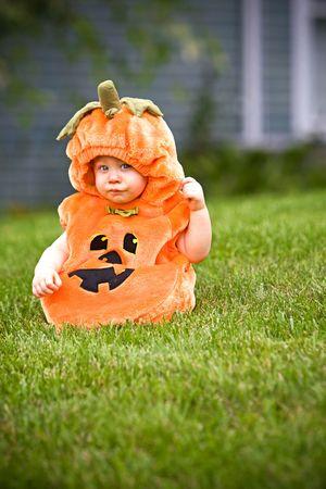Baby in a halloween pumpkin costume sitting on grass