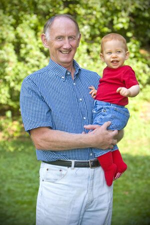 Grandfather holding happy grandson in sunny garden Stock Photo