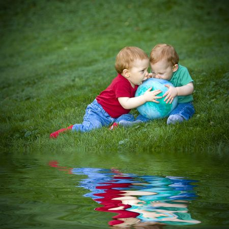 Young redheaded  boys sitting outside on grass playing with ball photo