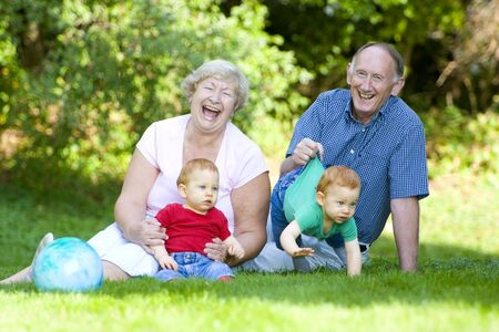 Playing with redheaded twin grandsons with focus on laughing grandparents photo