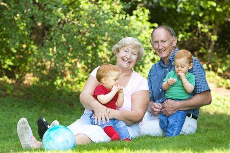 Happy handsome grandparents with twin grandsons outdoor portrait Stockfoto