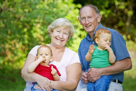 Holding redheaded twin grandsons with focus on happy grandparents photo