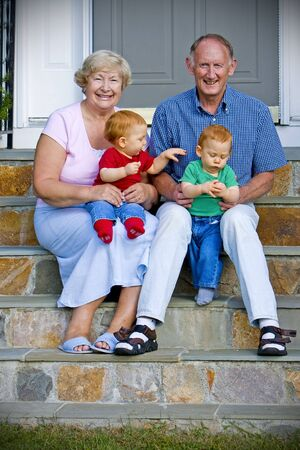Happy handsome grandparents with twin grandsons outdoor portrait photo