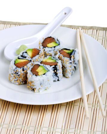 Raw fish and avocado sushi on a white plate with chopsticks and wasabi photo