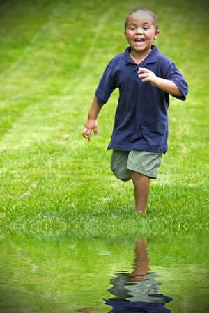 reflect: Happy mixed race boy running through green grass Stock Photo