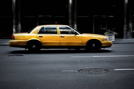 Dirty New York City yellow cab on road in evening