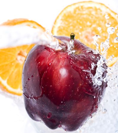 Water splashing down on an apple and oranges